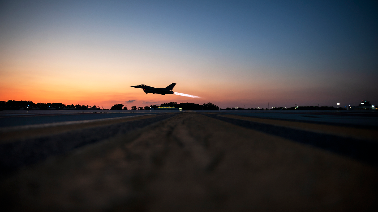 F-16 Fighting Falcon taking off at sunset..