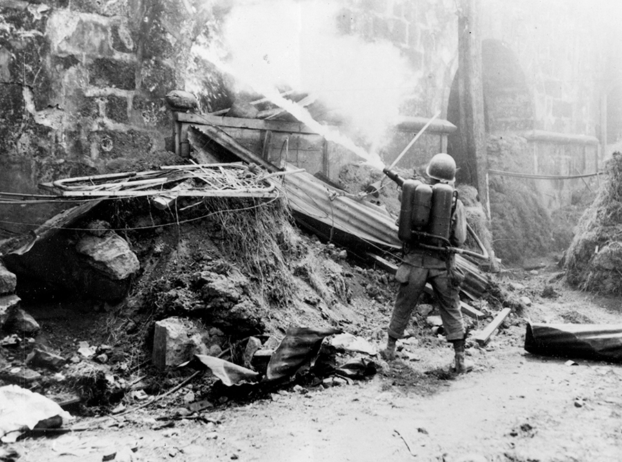 Soldier uses a flame thrower on a Japanese position.