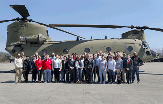 Group stand in front of Chinook helicopter.
