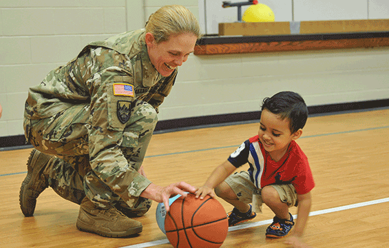 Solider kneels on floor next to child playing with basketball.