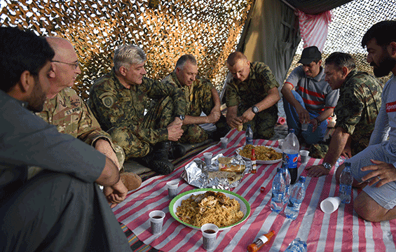 Soldiers sitting on floor of tent, sharing local prepared meal.