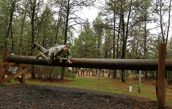 "Soldier going over large log ""hurdle-type obstacle""  in"