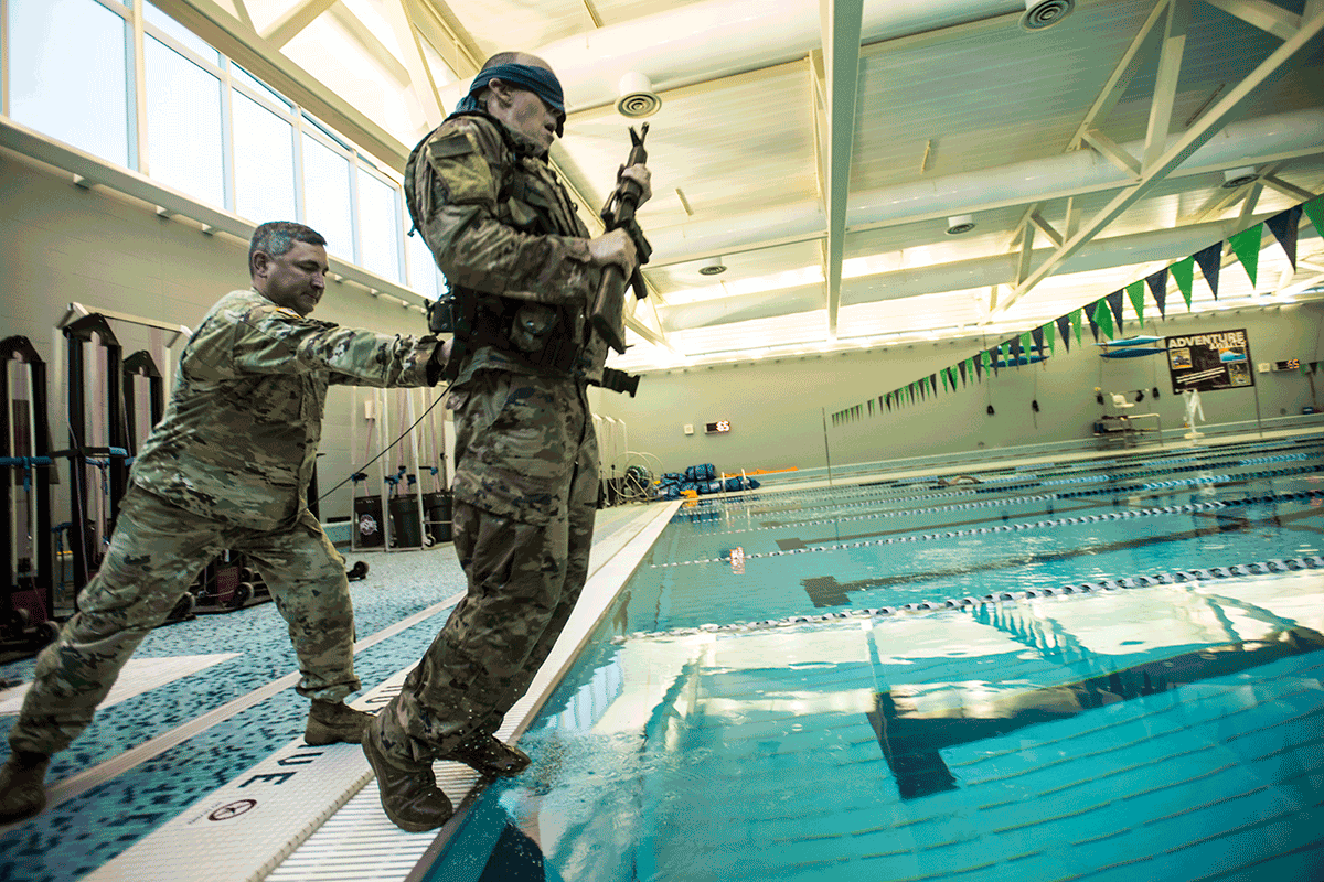 Airman pushes a blindfolded airman holding weapon into a swimming pool.