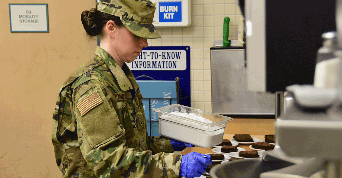Airman 1st Class Kelsey Bohachek sprinkles powder sugar on brownies.