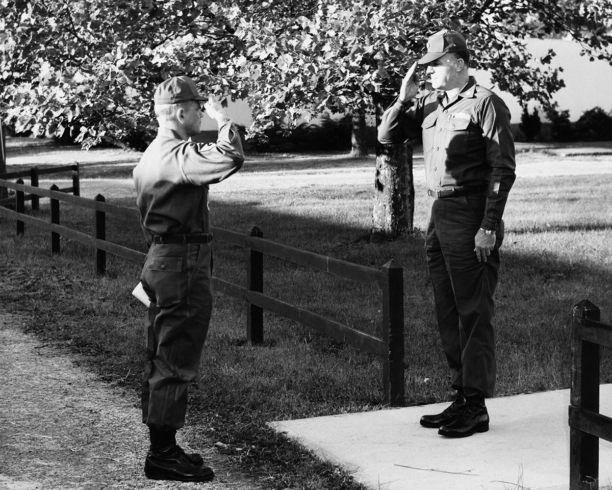 Black and white photo of first sergeant saluting squadron commander.