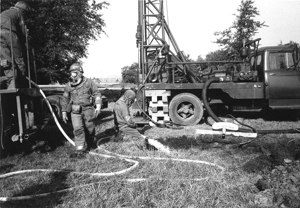 Members of the 200th RED HORSE operate a water well driller in chemical suits.