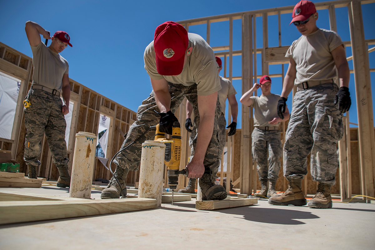 Airmen build cabin walls.