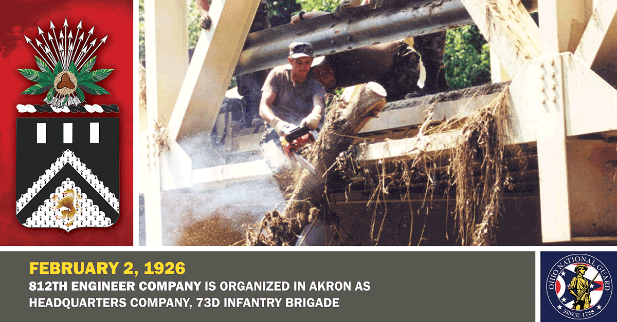 1998 photo: Spc. William Phelps of Company B, 112th Engineer Battalion, uses a chain saw to clear a fallen tree from a bridge