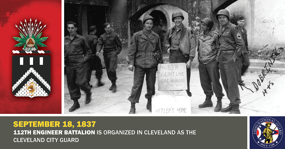 Soldiers pose for a picture in front of a sign that reads 'Hitler doesn't live here anymore. Why not?'