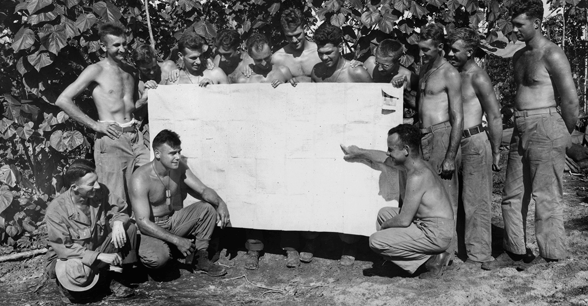 Black and white photo of shirtless Soldiers looking at large chart.