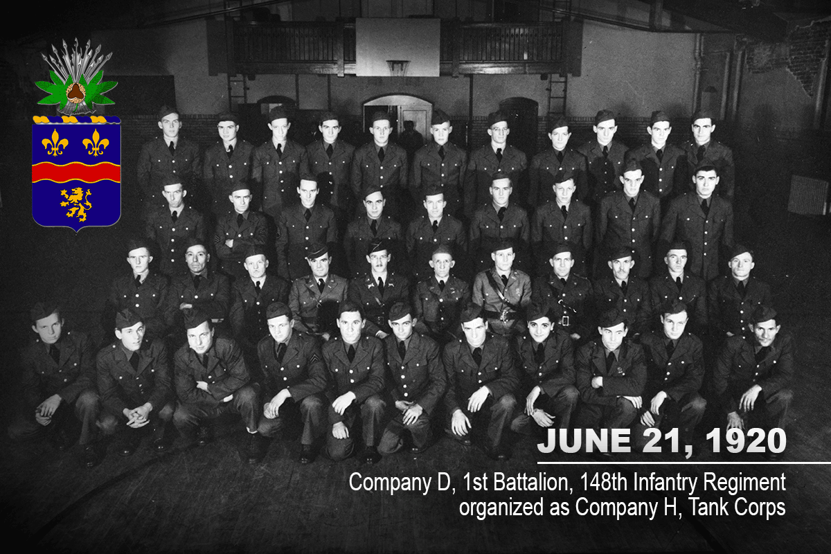 Black and white photo of Soldiers in dress uniform ligned up in rows for group shot inside building.