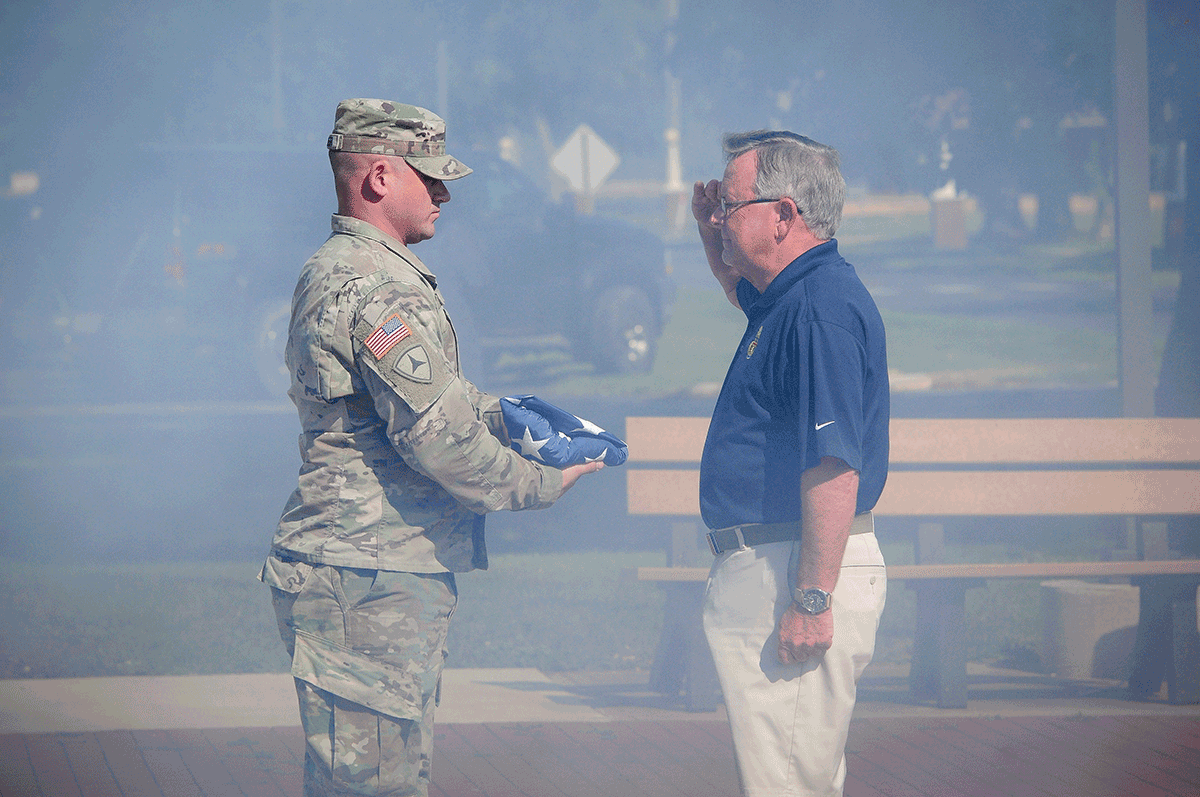 Soldier present folded flag to man saluting.