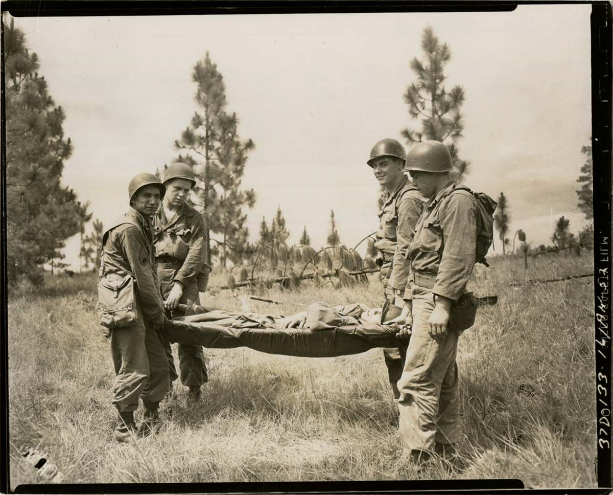 Sepia tone of Soldiers carrying injured Soldier off field on a gurney