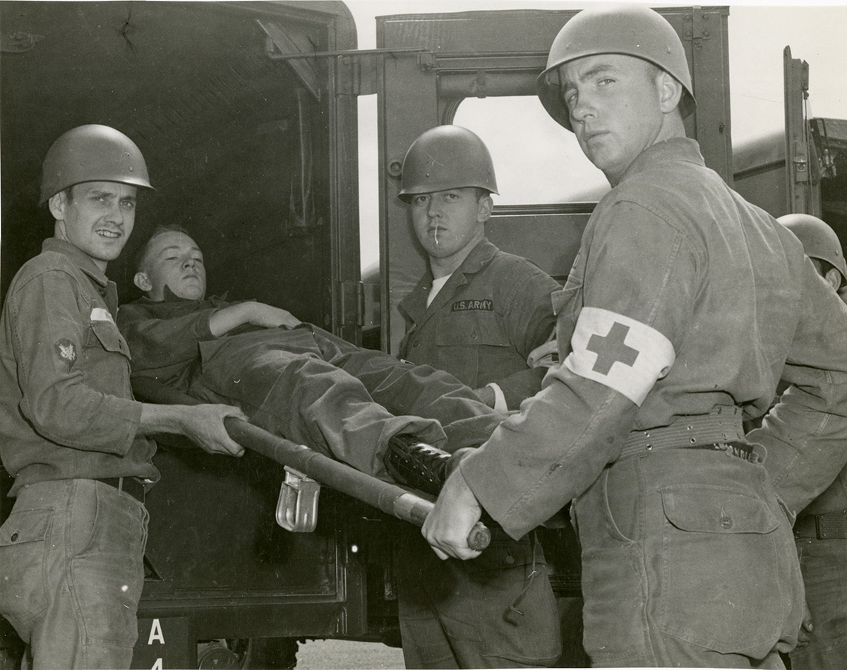 black and white photo of Soliders loading man on stretcher into back of a vehicle