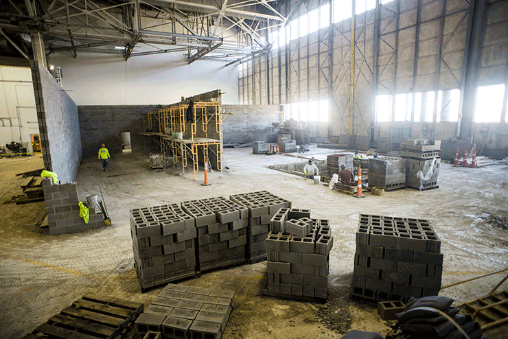 Construction site of simulator inside large empty building with pallets of concrete block all around.  Men working with concrete block.
