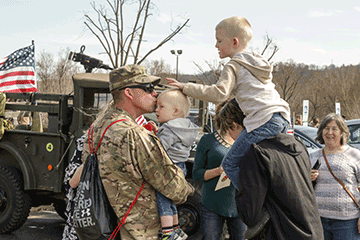 Soldier holds toddler, greets family.