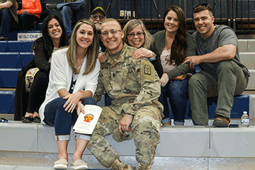 Soldier poses with his family on bleachers.