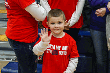 "Boy waves to camera wearing shirt that read "" OUTTA MY WAY I GET MY DADDY BACK TODAY"""