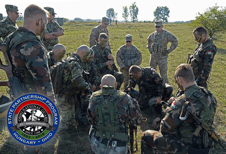 Ohio Soldiers review plans in field with hungarian Soldiers.