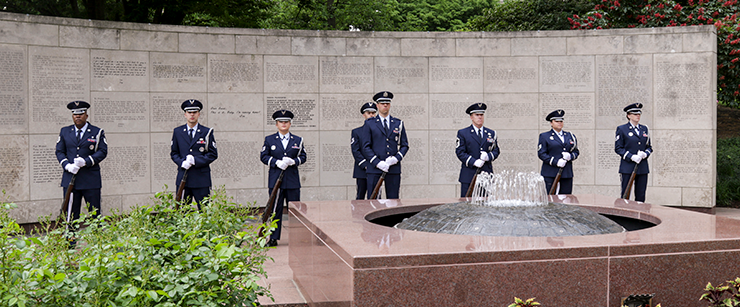 Airman honor guard stand in formation in fron to f wall monument with fountain in front.