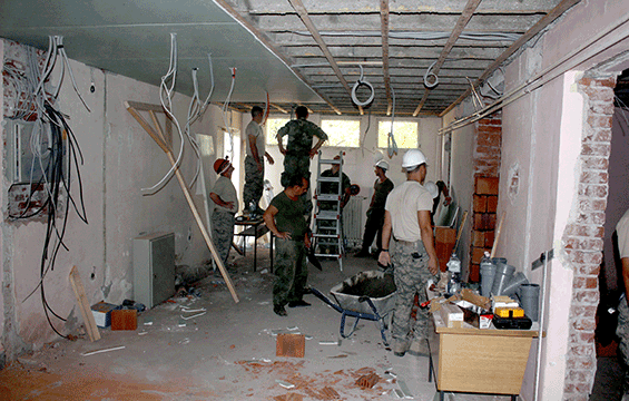 Soldiers working on cieling in school room.