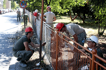 Soldiers painting chain linked fence on school grounds.