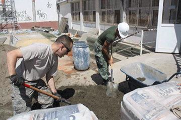 Soldiers mixing concrete outside school.