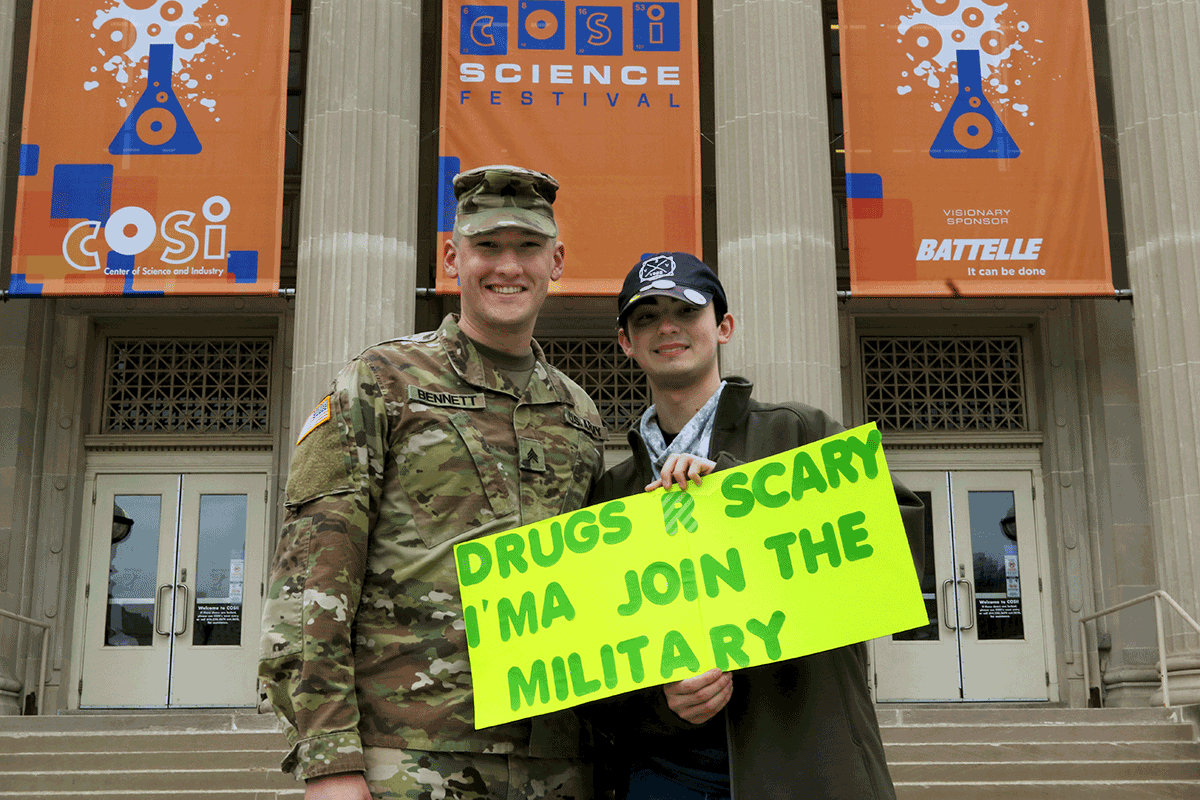 Soldier stands with student holiding sign that reads 'DRUGS R SCARY I'MA JOIN THE MILITARY' prior to march on steps of COSI.