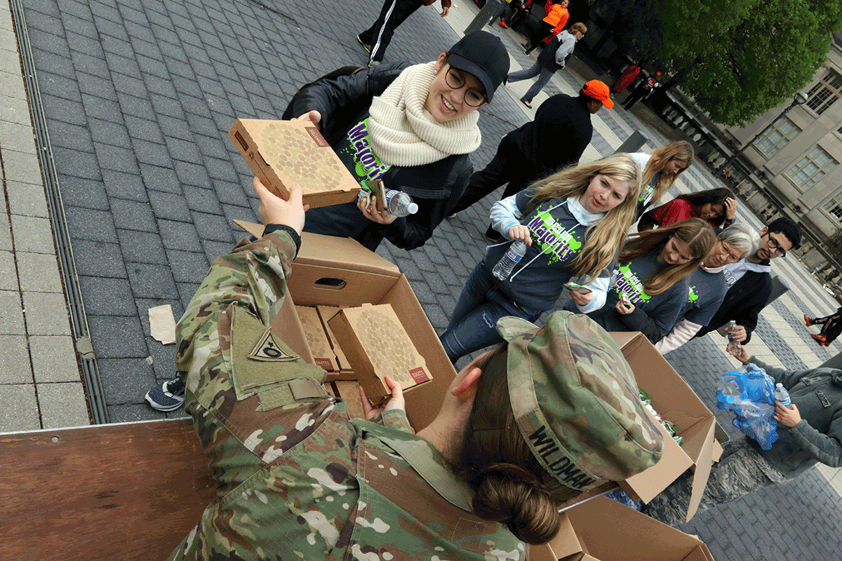 Soldier hands pizza to kids approaching the table.