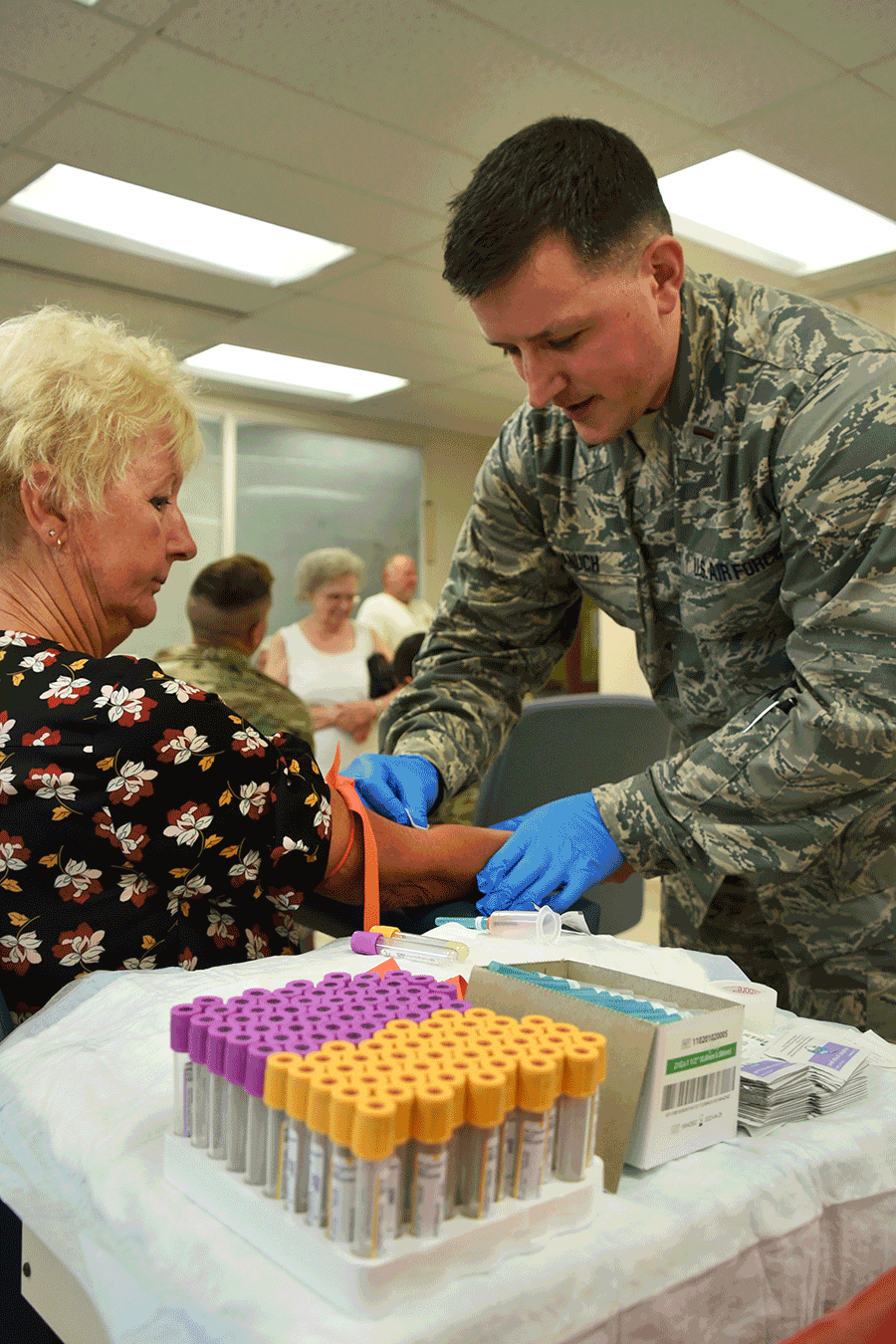 An Airman conducts a blood draw  on woman.