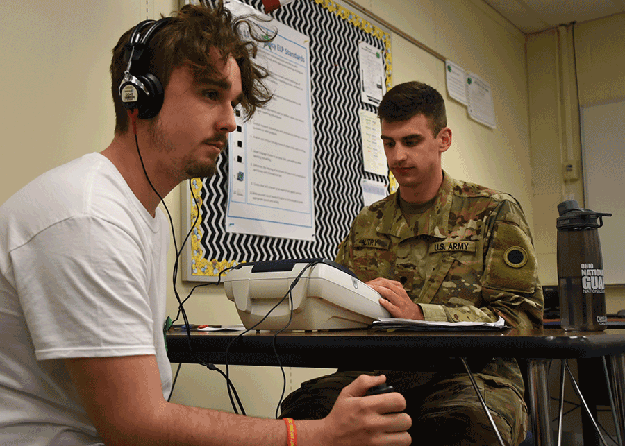 An Ohio Army National Guard health care specialist administers a hearing test to young man using a headset.