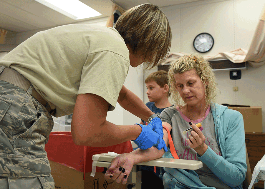 An Airman conducts a blood draw  on woman in chair.