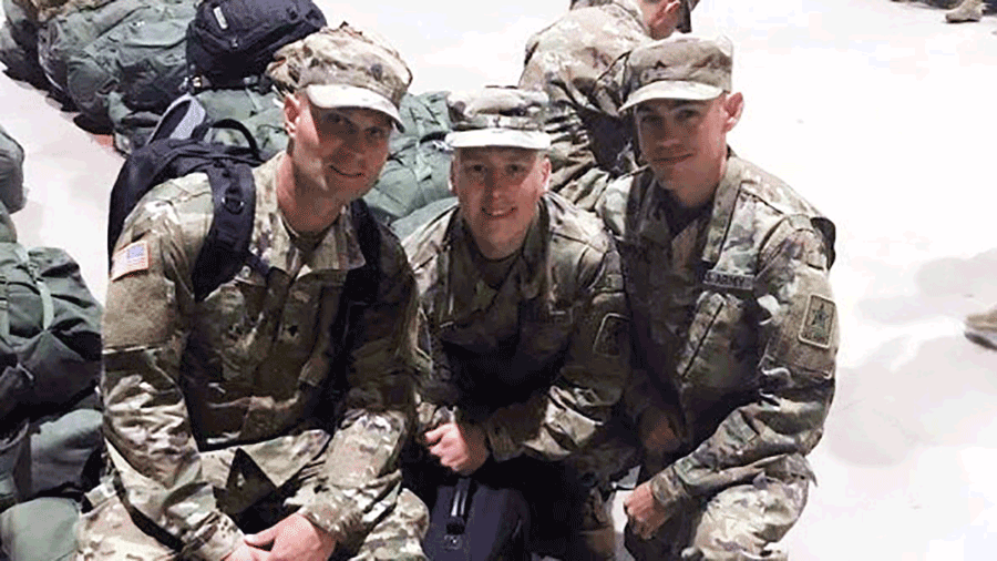 Three Soldiers in camo kneel together for photo