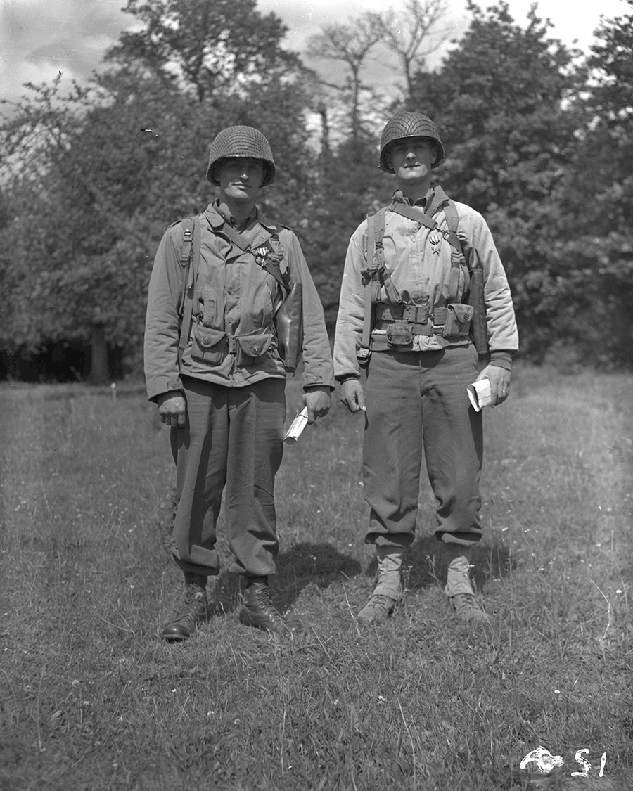 Black and white photo of 2 soldiers standing in field in full gear.