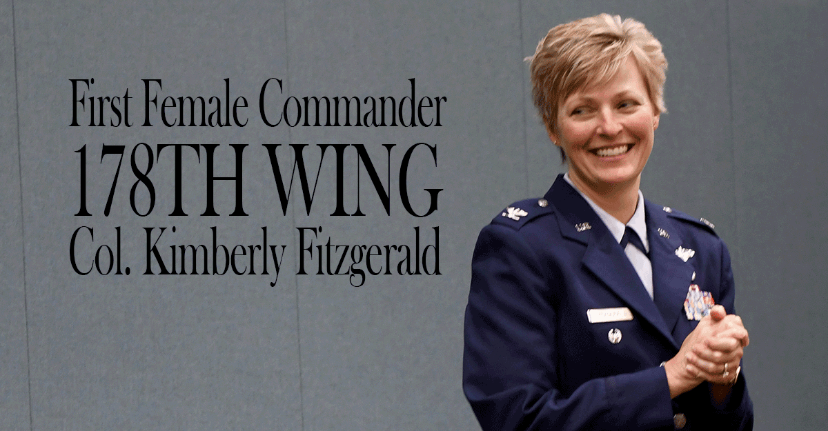 Col. Kimberly Fitzgerald stands in front of curtain.