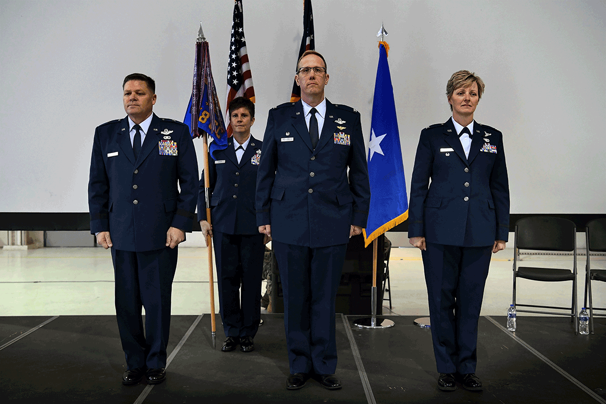 Commanders in formation on stage.