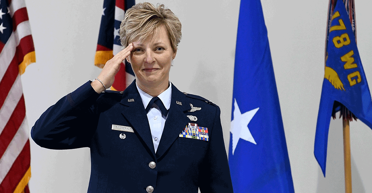 Col. Kimberly Fitzgerald salutes in front of flags.