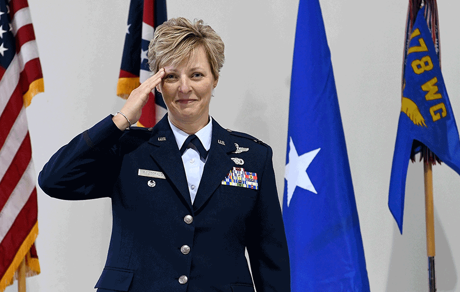 Col. Kimberly A. Fitzgerald salutes in front of the flags.