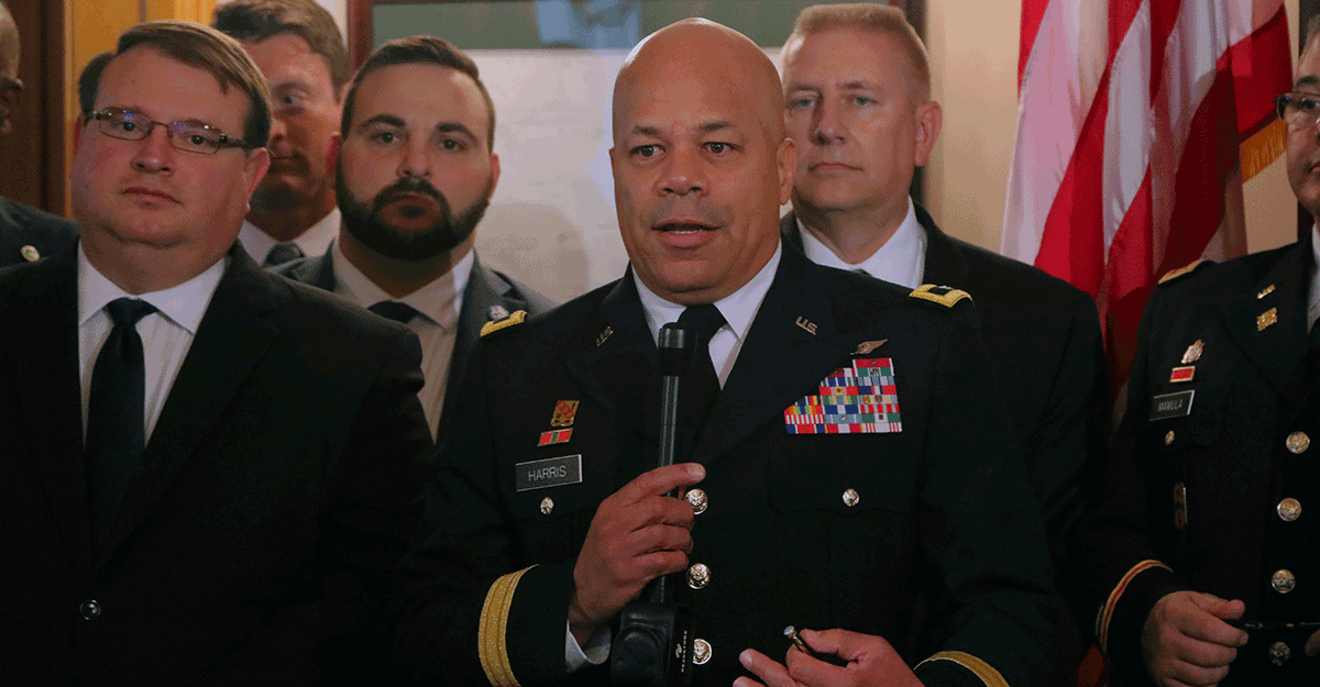 Maj. Gen John C. Harris, Jr. talks at podium with others standing around him.