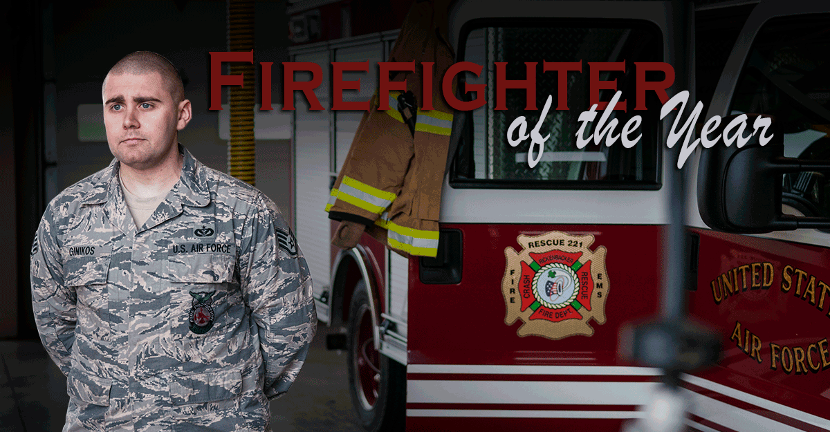 Staff Sgt. Michael Ginikos, in Air Guard camo, stands in front of firetruck.