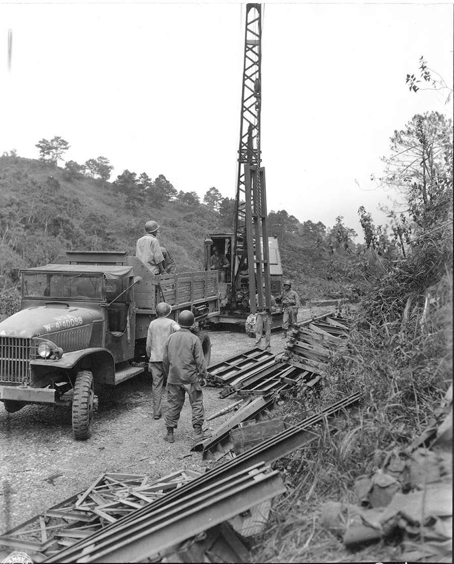 Soldiers construct a Bailey Bridge across a river.