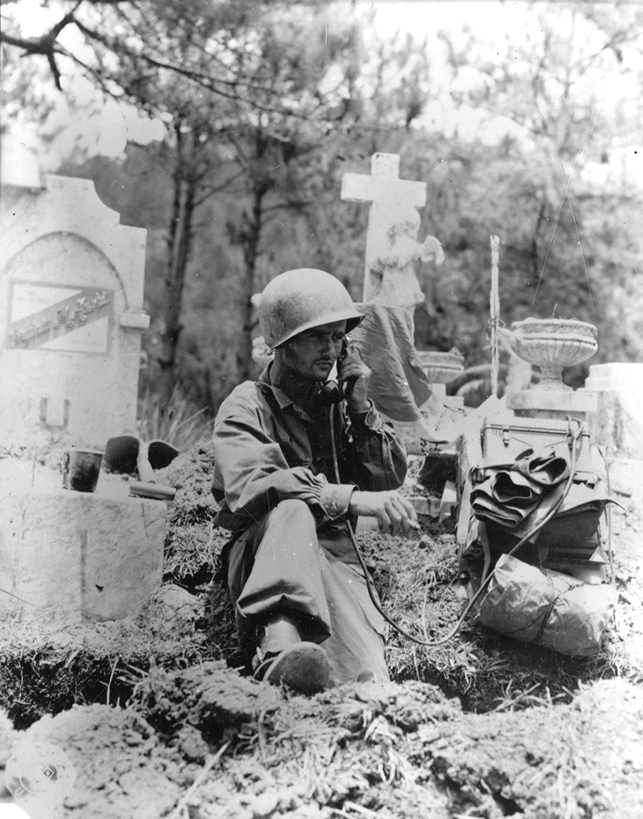 A radio operator is shown dug in at the cemetery.