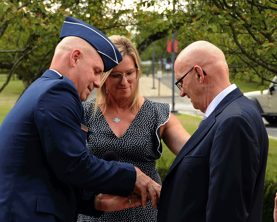 Brig. Gen. Gary McCue  presents a general officer's star rank to his father-in-law as his wife looks on.