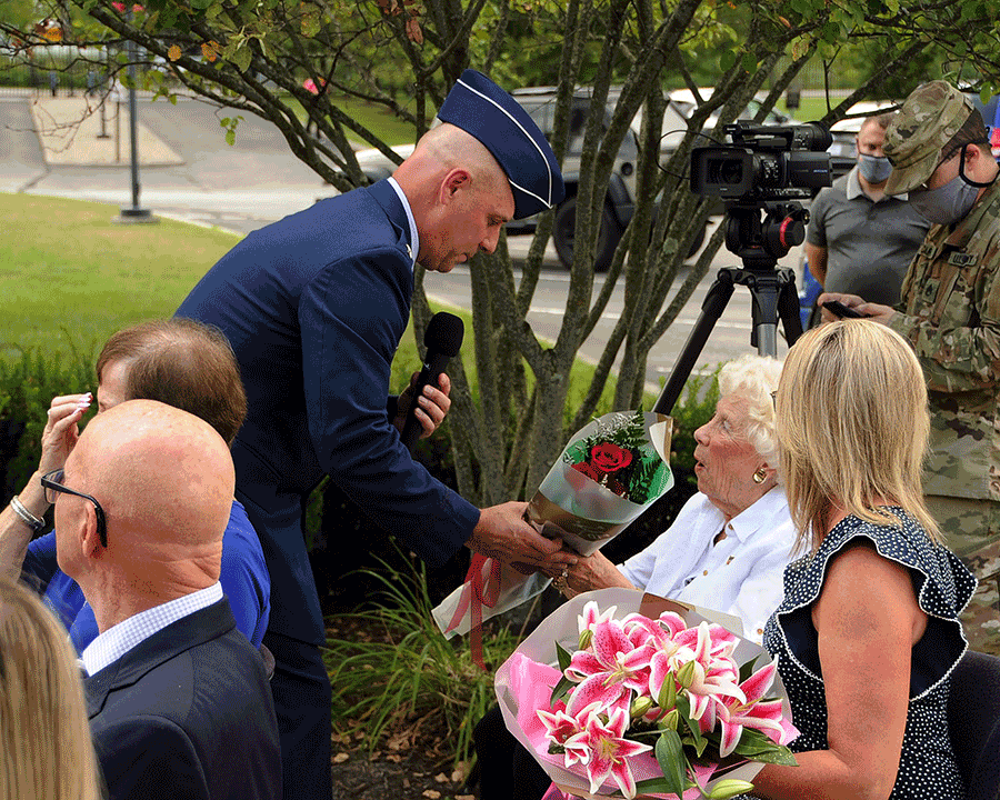 Brig. Gen. Gary McCue  presents flowers to his mother and wife.