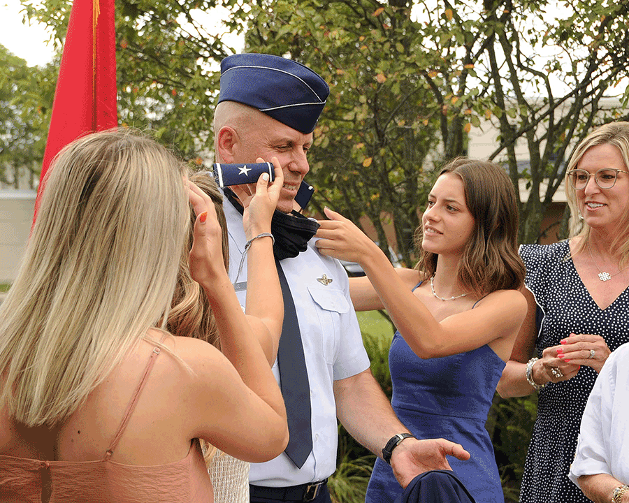 Family members affix new one-star shoulder boards on the epaulets of officer's uniform shirt.