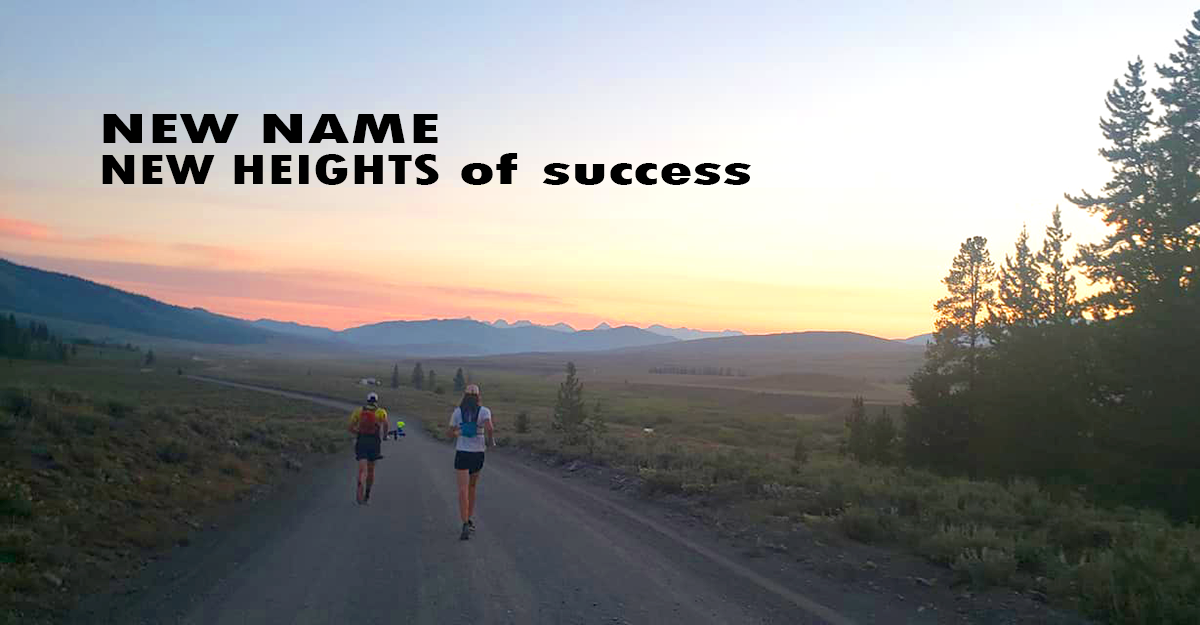 Team running on dirt road at sunrise with mountains in distance.
