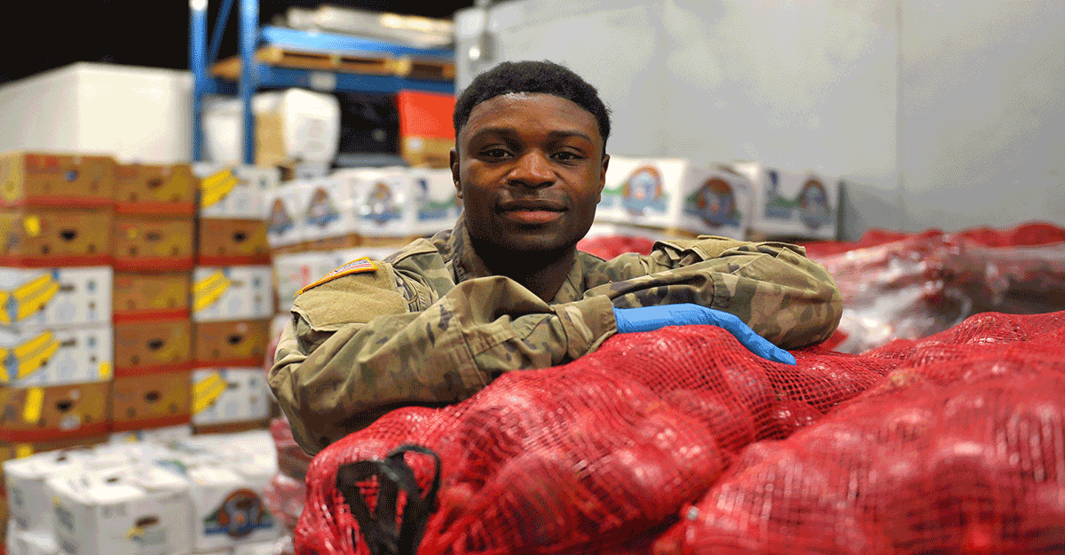 Spc. Jacque Elama stands for photo at food bank.