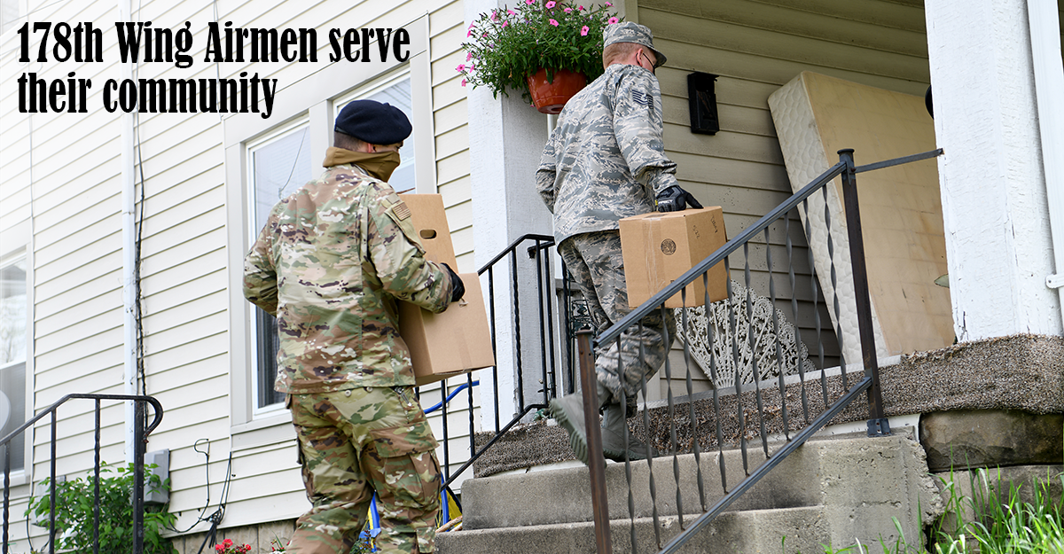 Two guard members carry boxes of supplies up steps to a beige house.