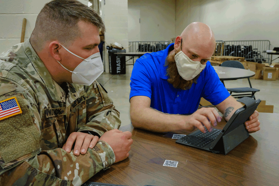 Soldier watches civilian at table working on laptop.