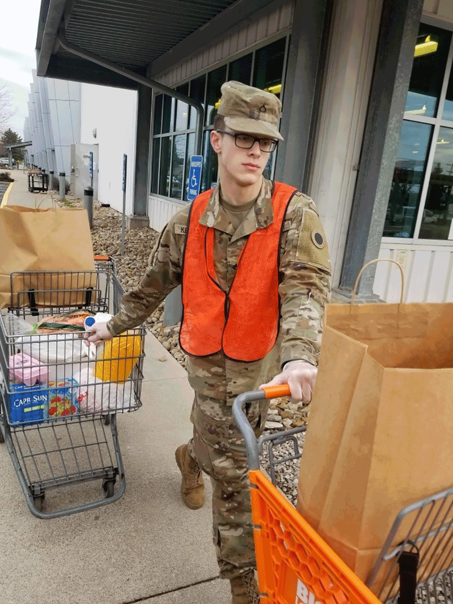 Soldier wheels out grocery carts of supplies.